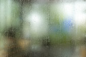 Misted glass, silver rain drops dew drops on transparent glass window. Wet misted glass with drops of water and dew.