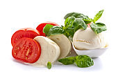 Mozzarella  with tomatoes and green basil isolated on white background .