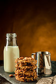 Oatmeal cookies with milk on table. Chocolate chip cookies with milk. Healthy food and drink and natural diet food. Cookie Almond and Cashew nuts.