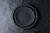 Empty black plate on a black background. Top view.