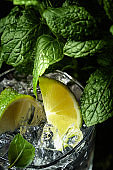 Drink with lime, ice and mint on dark background.