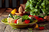 Green salad with mozzarella, tomato and basil in green plate on a old wooden background.