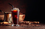 Ice coffee in frozen glass and coffee beans on a old brown table with kitchen utensils.