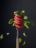 Sliced smoked sausage with green basil leaves.