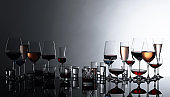 Various alcoholic beverages in glasses on a black reflective background.