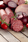 Food tray with delicious salami, ham, fresh sausages, tomato, and rosemary.