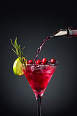 Cranberry cocktail garnished with berries, lime, and rosemary.