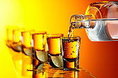 Pouring a strong alcoholic drink into small glasses.