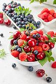 Various juicy berries with leaves.