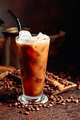 Ice coffee with cream being poured into it showing the texture and refreshing look of the drink.