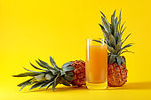 Fresh ripe pineapples and juice on a yellow background.