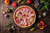 Tasty hot italian pizza with Bacon, Salami, Ham, Cheese Mozzarella, Parmesan, Peppers, Mushrooms, Pepperoni, Tomato Sauce on old wooden table. Pizzeria menu.