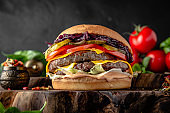 Tasty grilled double big burger with beef, cheese, vegetables.  Delicious grilled hamburger on a dark background.