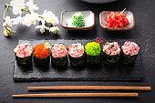 Gunkan sushi set with salmon, tuna, perch, eel, scallop, caviar, shrimp, sharp.  Traditional Japanese cuisine. Black background.