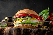 Tasty Diet fitness burger with chicken cutlet, avocado, caramelized onions and vegetables.  Delicious low-calorie, nutritious, healthy hamburger on a dark background.
