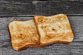 Two square ruddy pieces of bread for toasts on the old gray wooden background