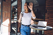 Woman in casual outfit with coffee smiling and waving hand