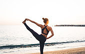 Fit young woman standing in Hasta Padangusthasana yoga posture on sandy seashore at sunset