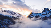 Scenery aerial view, drone flying through clouds to mountain snowy pines with frost in winter, bird's eye view of beautiful nature landscape under breathtaking sky