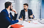 Confident male executive managers 30s discussing business strategy during working process at table desktop, Caucasian investors in formal wear have collaborative brainstorming in office interior