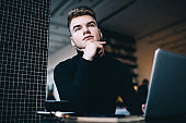 Concentrated young man working remotely in modern workspace