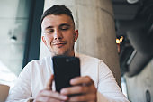Smiling male browsing smartphone in cafe