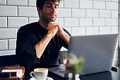 Pensive ethnic man working on laptop