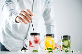 Bartender puts striped drinking straw in jar with fresh cold homemade lemonade made from ice, strawberry, orange, cucumber and mint. Close focus