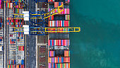 Container Cargo freight ship with working crane loading bridge, Container ship loading and unloading in deep sea port, Aerial view of business logistic import and export freight transportation .