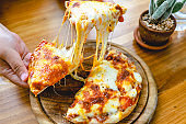 A slice of fresh hot Very cheesy vegetarian pizza mozzarella cheese. Italian Pizza Margherita in hand