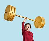 Cute child lifting gold barbell on blue pastel background. He is a determined and successful child.