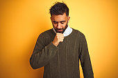 Young indian man wearing green sweater and shirt standing over isolated yellow background feeling unwell and coughing as symptom for cold or bronchitis. Healthcare concept.
