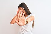 Young beautiful woman wearing casual t-shirt standing over isolated white background covering eyes with hands and doing stop gesture with sad and fear expression. Embarrassed and negative concept.