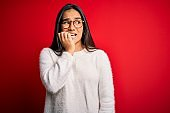 Young beautiful asian woman wearing casual sweater and glasses over red background looking stressed and nervous with hands on mouth biting nails. Anxiety problem.