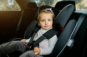 Transport, safety, childhood road trip and people concept. Happy Caucasian cute little baby girl sitting in baby car seat. Child in auto baby seat in car. Adorable little girl in the car.