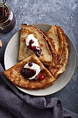 Traditional homemade pancakes with cranberries and sour cream served on gray stone table Vertical Top view.
