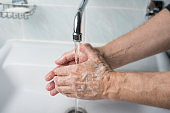 Older male is washing his hand under faucet
