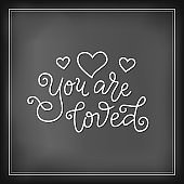 calligraphy lettering of You are loved in white with hearts on chalkboard