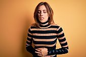 Young beautiful brunette woman wearing striped turtleneck sweater over yellow background with hand on stomach because indigestion, painful illness feeling unwell. Ache concept.