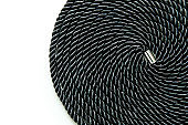 The rolled up black soft bondage rope isolated in a white background.