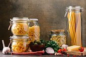 Different pasta in glass jars and ingredients for Italian cuisine on the table