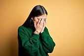 Young beautiful asian woman wearing green winter sweater over yellow isolated background with sad expression covering face with hands while crying. Depression concept.