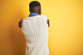 African american man wearing denim shirt and white sweater over isolated yellow background Hugging oneself happy and positive from backwards. Self love and self care