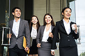Asian business people walking to go out office building. Young businessman and businesswoman talking and Open the office door.