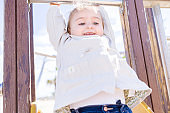 Beautiful toddler child girl wearing jacket playing with slide on the beach