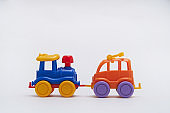 Colored toy cars collided in an accident on a white background Crash on a toy road
