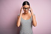 Young beautiful woman wearing casual striped dress and glasses over pink background suffering from headache desperate and stressed because pain and migraine. Hands on head.