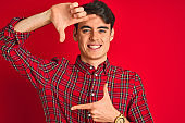 Teenager boy wearing red shirt standing over isolated background smiling making frame with hands and fingers with happy face. Creativity and photography concept.