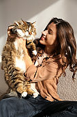 Charismatic young woman playing with her adorable cat.