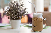 Ice coffee latte with white straw in the glass, Refreshing with cold beverage, Energetic drink concept
